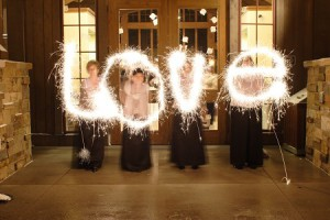 4 bridesmaids spelling the word love with sparklers