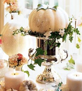 White pumpkin set a top a silver urn. Ivy draped asymetrically.