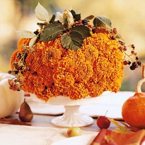 orange flowers in shape of pumpkin, leaves and stem added to top. sitting on white cake stand.