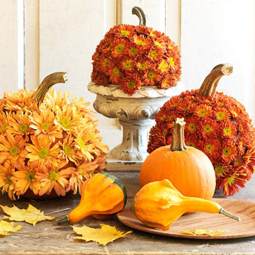 mums and daisies inserted into pumpkins