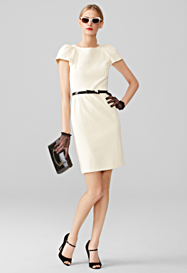 ivory dress with puff shoulders accessorized with black belt, heels, and gloves